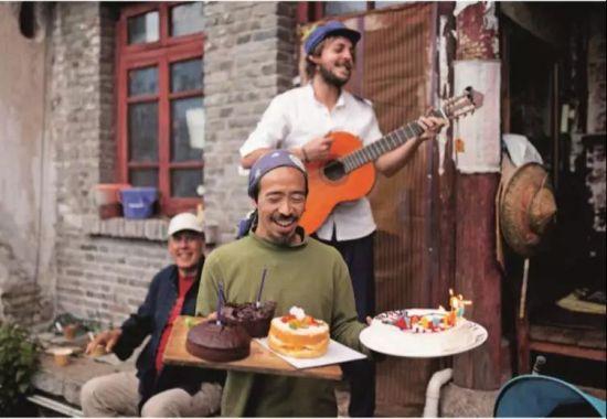 六的朋友约翰给孩子们弹唱生日歌。他们来自不同的国家,有相似的志趣、爱好和经历,差不多都是在漫长的旅程中漫游,到了一个很小的地方,停留下来,按照各人的条件慢慢开创小家庭的生活,未来或许还将远行。