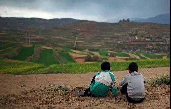 2015年4月,甘肃陇南,傍晚时分,两名干完活的留守儿童在地里休息,看着远方。他们的父母去了城市里打工,一年回来一次。摄影/刘飞越
