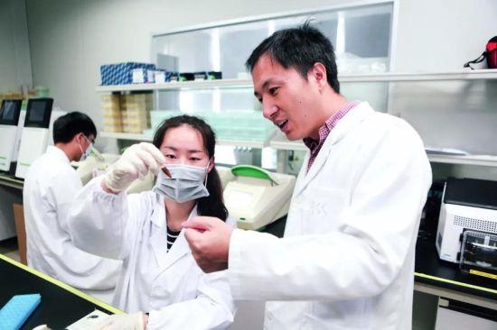 深圳市瀚海基因生物科技有限公司内,贺建奎(右)与实验室的工作人员。 图/视觉中国