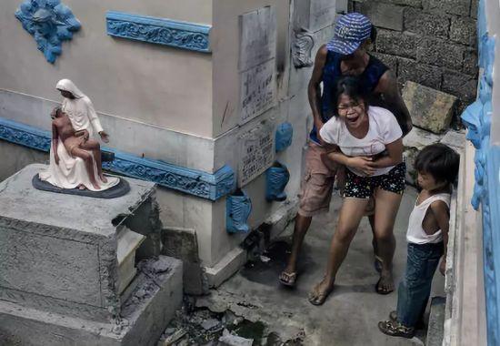一位年轻的母亲正在亲手埋葬 自己的儿子