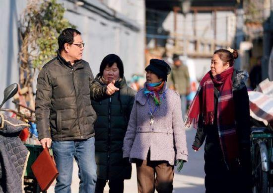 2017年12月13日,刘跃明(左一)与街巷居民蔡阿姨(右二)和社区工作人员一起在街巷内巡视了解情况。刘跃明是北京市东城区人民市场东巷街巷长,责任街巷总长204米。图/新华