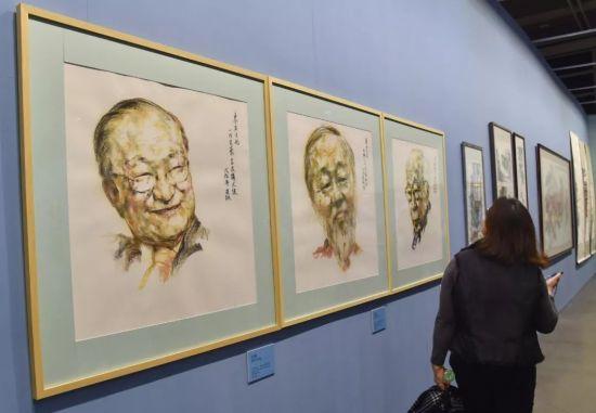 """12月19日,""""香港牵动我的心-庆祝改革开放40周年美术创作展""""上,三幅分别画有金庸、高锟、及饶宗颐的画作,展示在一起。"""