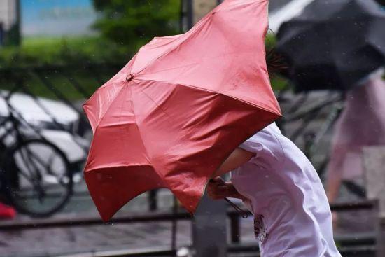 台风山竹影响广州,外出的市民在风雨中狼狈前行。